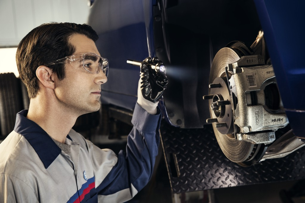 A mechanic looks at a brake inquisitively.