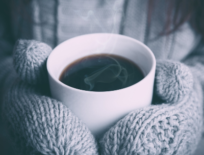 Two hands with mittens hold a steaming cup of hot cocoa.