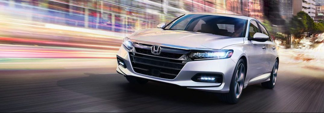 White 2020 Honda Accord drives at high speed up a city street.