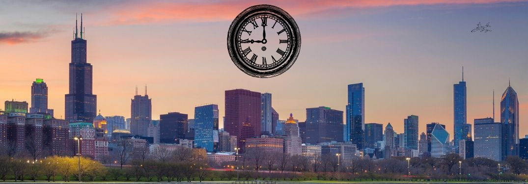 A large clock looms over the Chicago skyline at twilight.