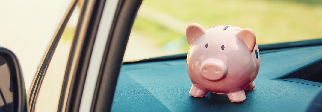 A pink piggy bank sits on the blue dash shelf of a vehicle.