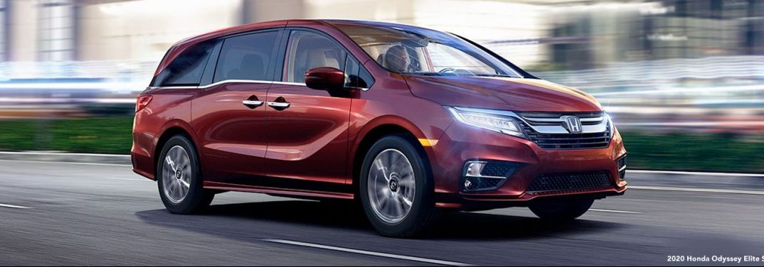 A red 2020 Honda Odyssey drives up a city highway.