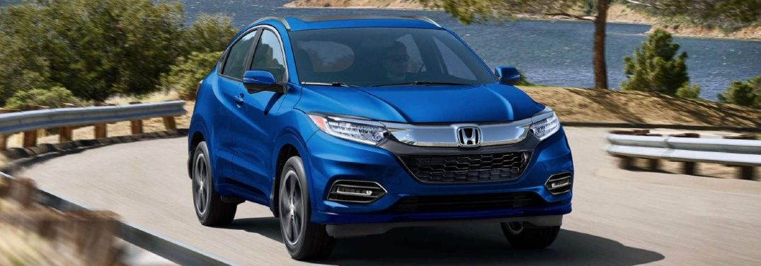 Blue 2020 Honda HR-V drives up a curvy highway.