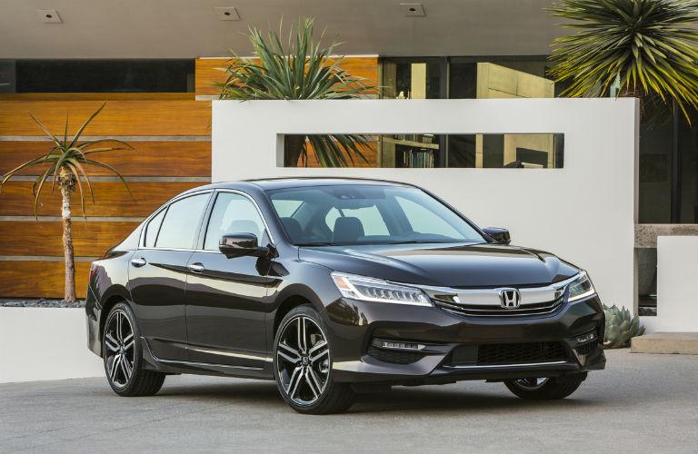 Shiny 2017 Honda Accord sedan sits parked outside a modern house in the tropics.