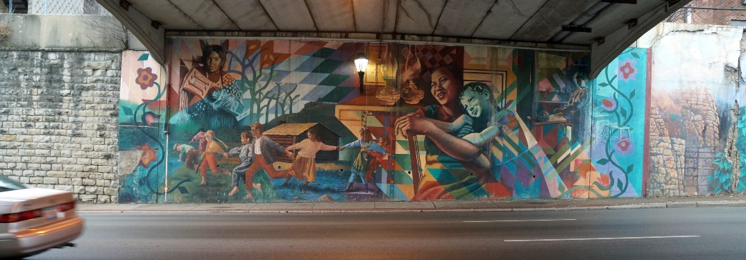 A detailed mural adorns the wall of a Chicago underpass.