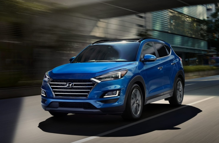 Exterior view of a blue 2019 Hyundai Tucson driving underneath an overpass