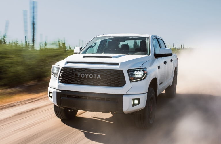 Exterior view of a white 2019 Toyota Tundra driving down a dirt road