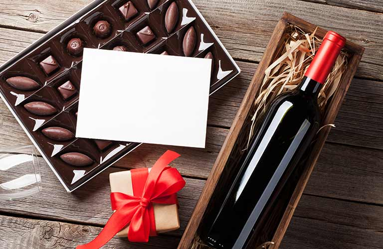 Image of a bottle of wine and a box of chocolate on sitting on a wooden table