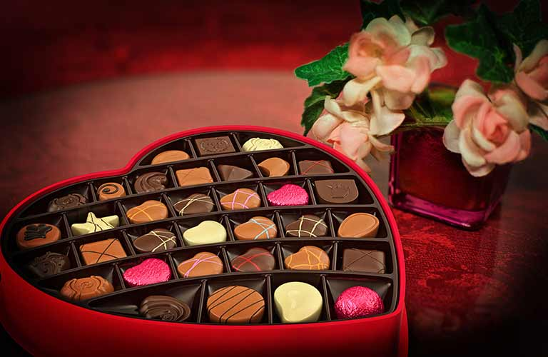 Image of a heart-shaped box full of various chocolates