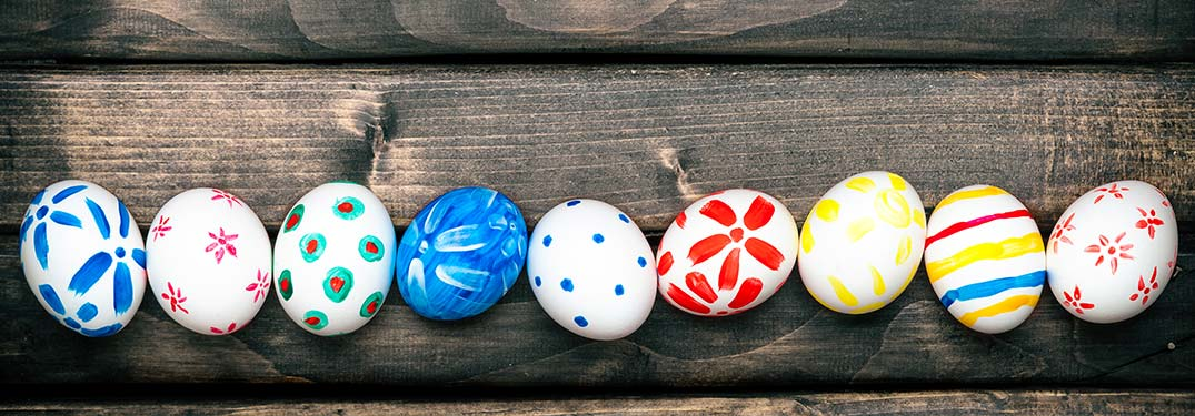 Image of several multi-colored Easter Eggs in a row on a wooden table