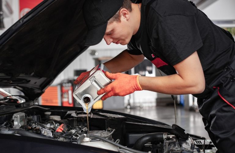 Image of a mechanic pouring oil into an engine