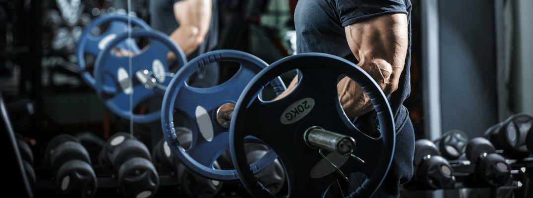 Man doing bicep curls with bar inside gym