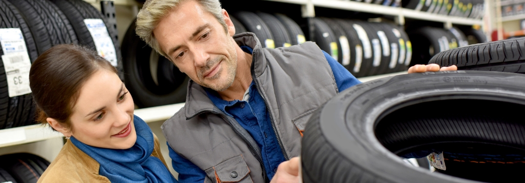man helping woman find tires at auto shop
