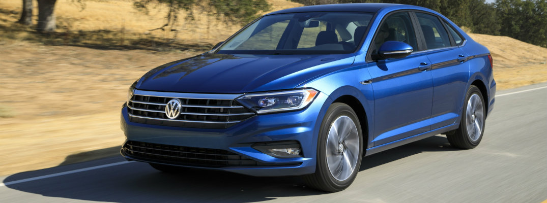 Blue 2019 Volkswagen Jetta parked on hilly backdrop