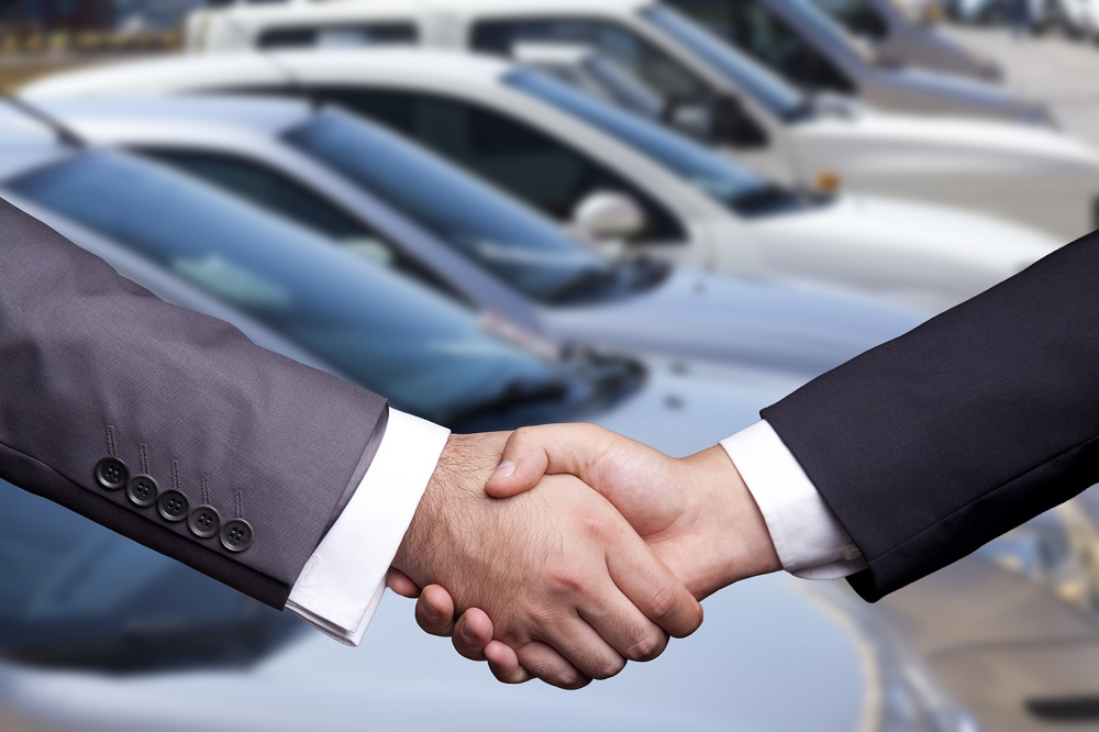 Handshake in Front of Cars