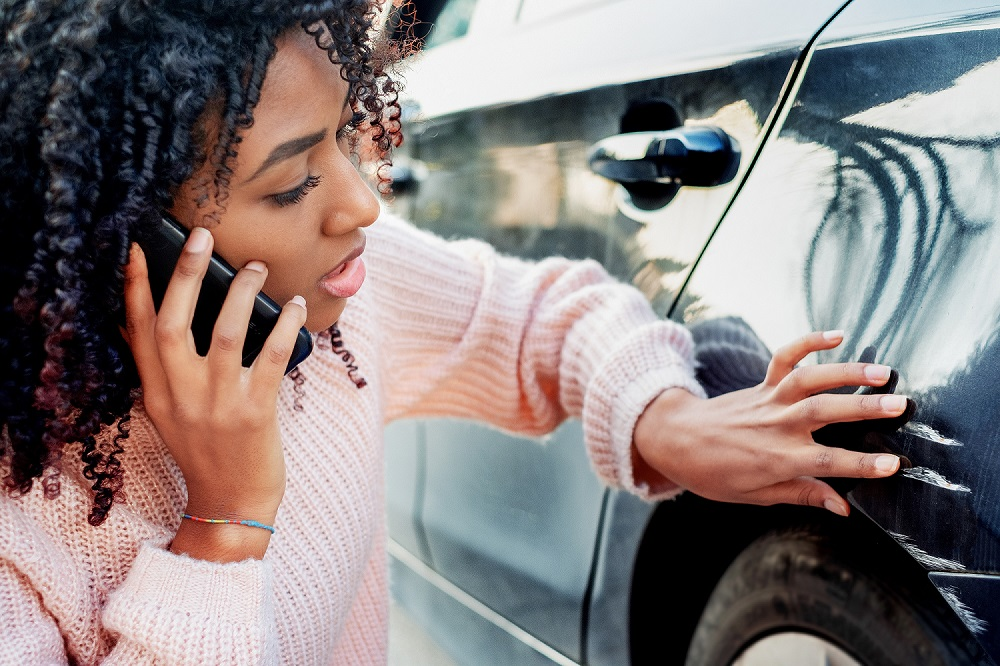 Woman on phone examining damage to car