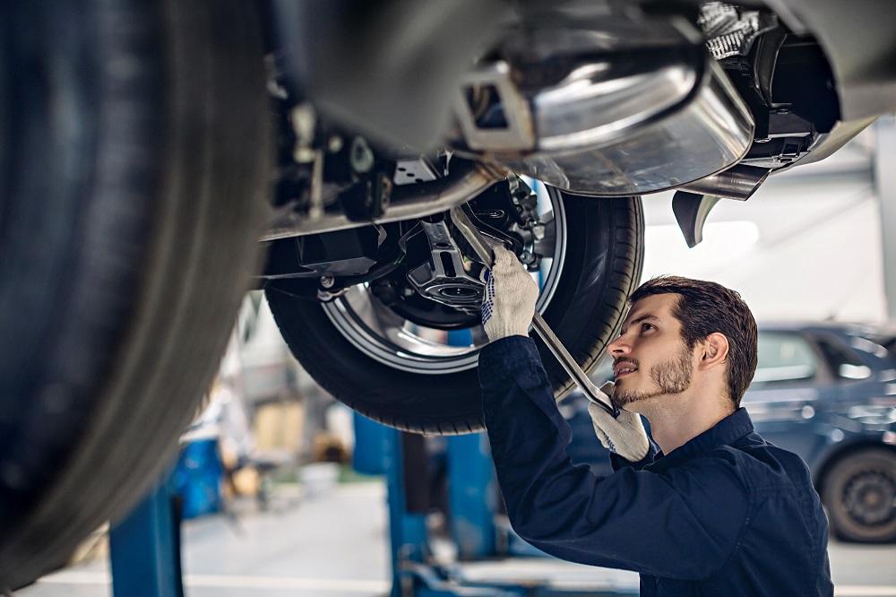 Mechanic Tuning Up Car