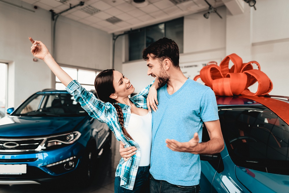 Couple in front of car with bow