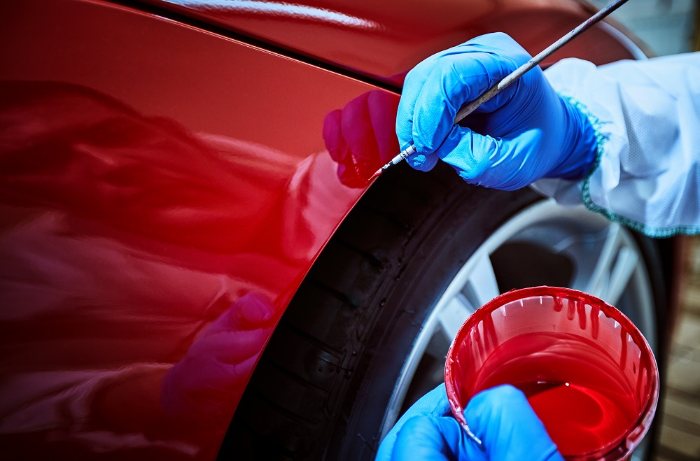 Man Touching Up a Red Car with a Fine Paintbrush