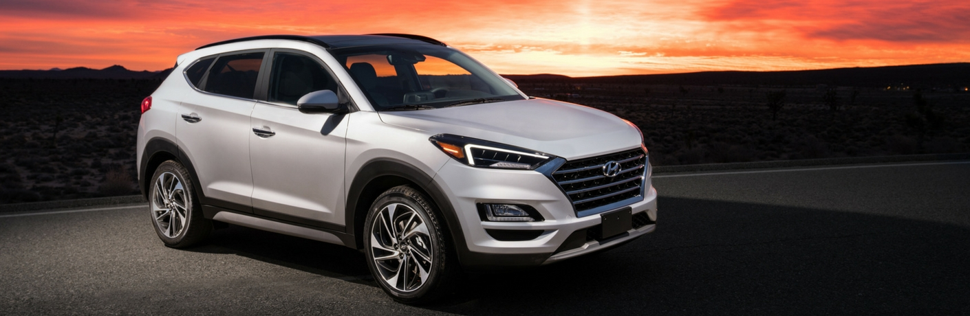 white hyundai tucson in front of a sunset