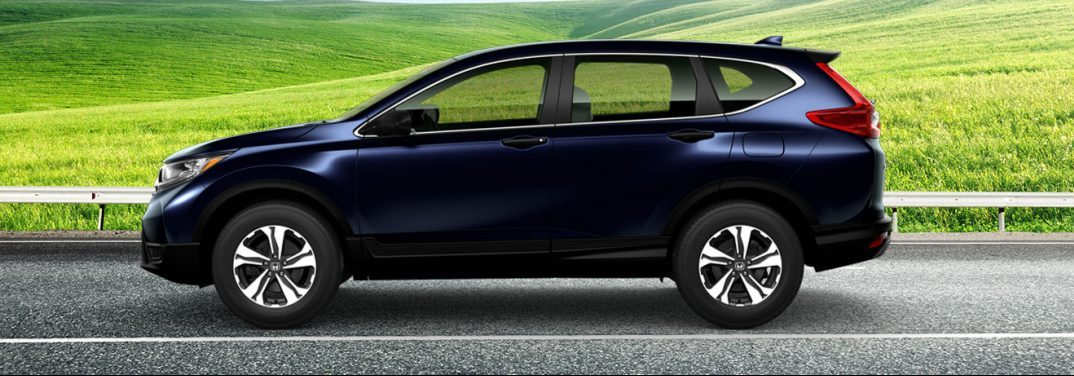 Purplish black 2019 Honda CR-V on a highway against a green field background, viewed from the side. It may or may not be bigger than past models.