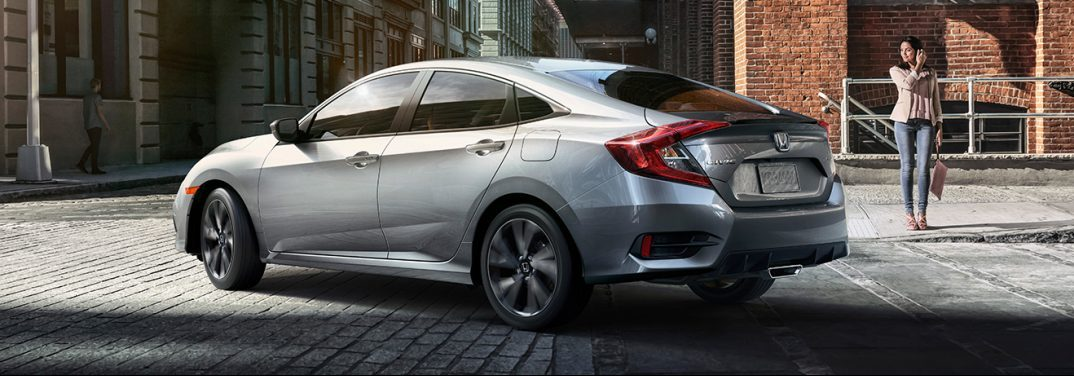 Silver 2019 Honda Civic turns a corner on a cobblestone street.