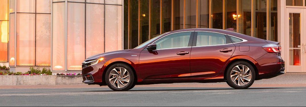 Crimson Pearl 2020 Honda Insight parked outside a building and viewed from the side at sunset.