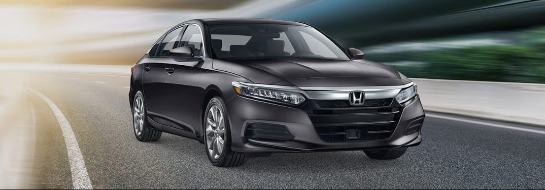Black 2019 Honda Accord Sedan drives down a highway.