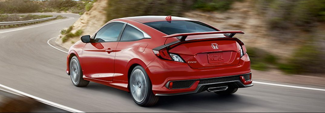 Red 2019 Honda Civic Coupe drives along a winding mountain highway.