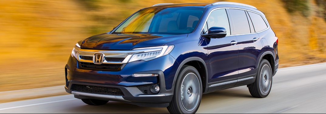 Blue 2019 Honda Pilot drives down a highway beside a yellow mound.