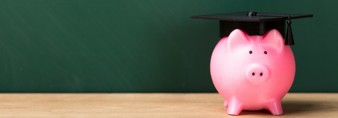 A pink piggy bank wears a graduation cap in front of a green chalkboard.