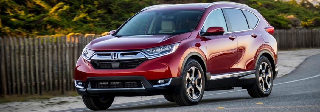 Red 2019 Honda CR-V cruises down a suburban road.