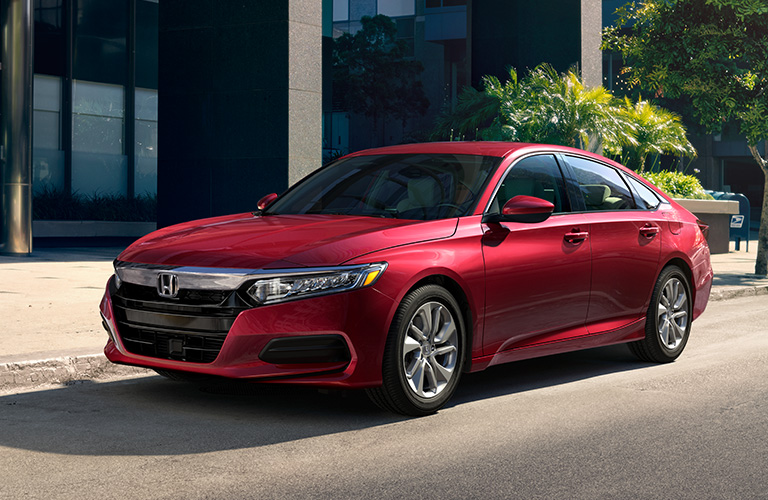 Red 2019 Honda Accord parked outside a modern building.