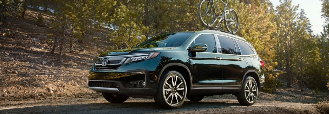 Green 2020 Honda Pilot with Bike on Roof on Country Road