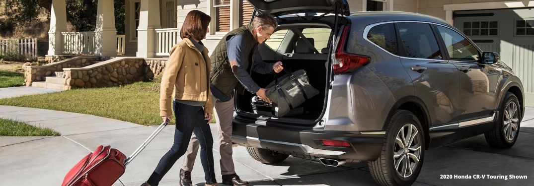Man and Woman Loading Luggage in the Back of a 2020 Honda CR-V with White 2020 Honda CR-V Touring Shown Text in Lower Right
