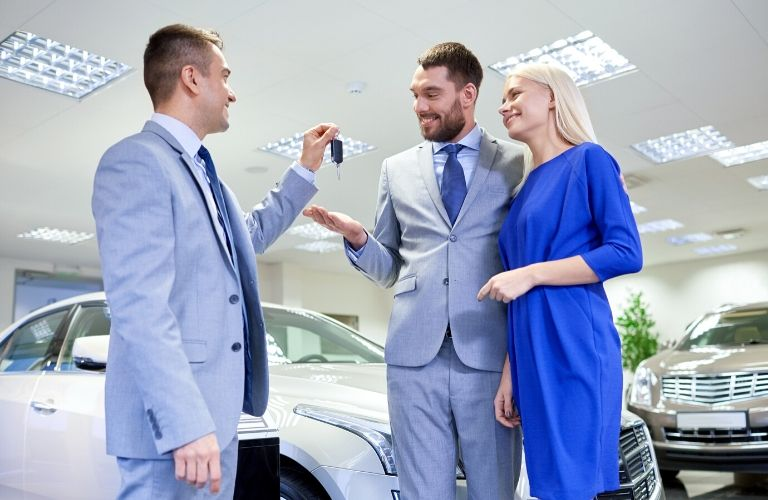 Salesman Handing a Couple Keys to a New Car