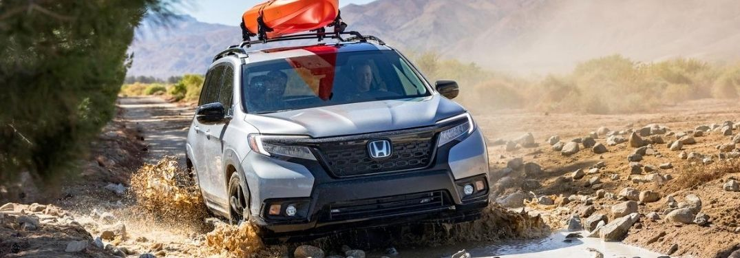 Silver 2020 Honda Passport Crossing a River with Orange Kayak on Top