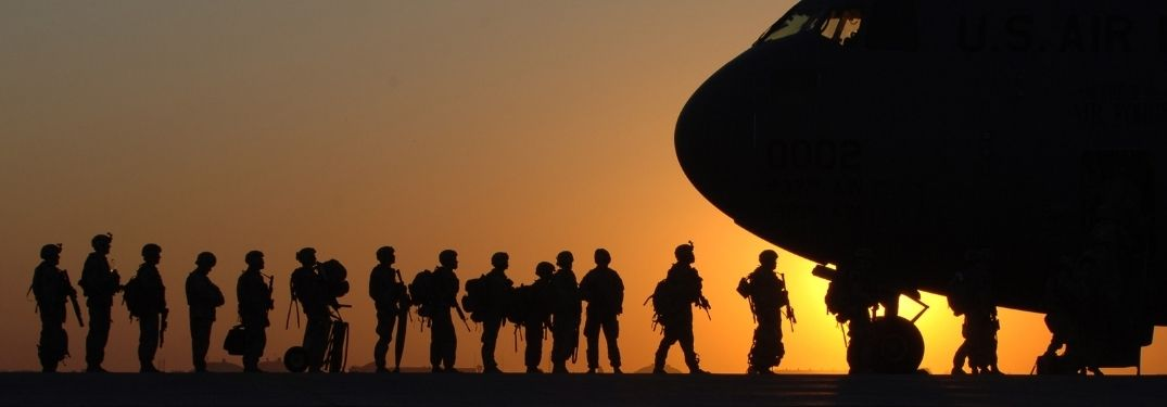 Silhouette of Soldiers Loading into an Airplane