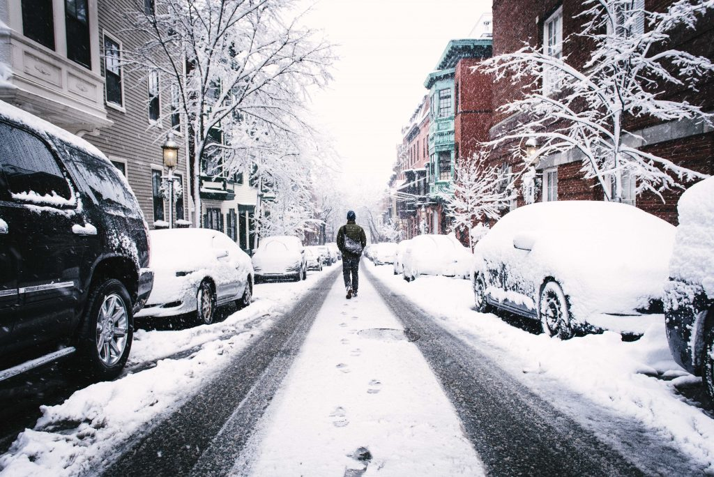 a man walking down a snowy road in the city near snow covered cars