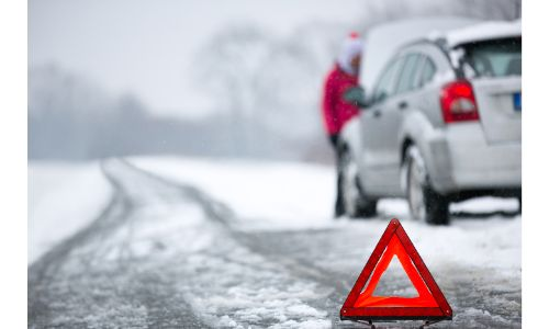 stock photo of car on side of snowy road with orange pop up reflector