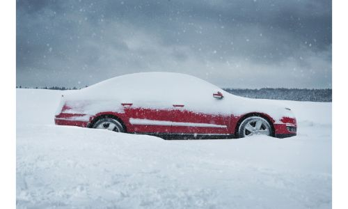 stock photo of red car buried in snow with low atmospheric light