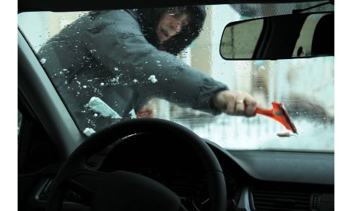 young man scraping ice off a windshield picture shot from inside vehicle