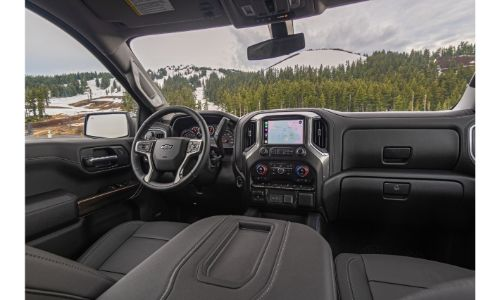 2020 Chevrolet Silverado 1500 interior shot from center console showing both seats steering wheel dashboard and screen on nav