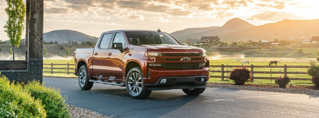 2020 Chevrolet Silverado 1500 red paint parked on asphalt with green field and mountains behind sunset building on left