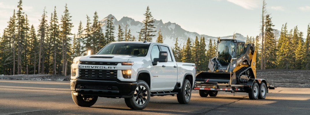 2020 Chevrolet Silverado HD pulling equipment on a trailer down a forested road with mountain background