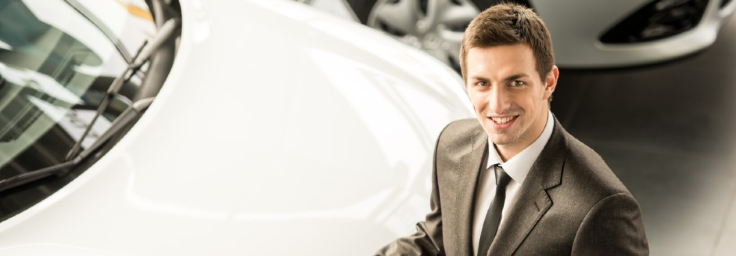 salesperson smiling up next to white car