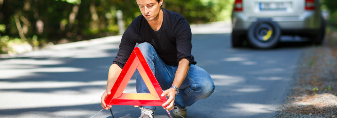 How to Make a Roadside Emergency Kit with image of a guy putting a triangle reflector on the road behind his car