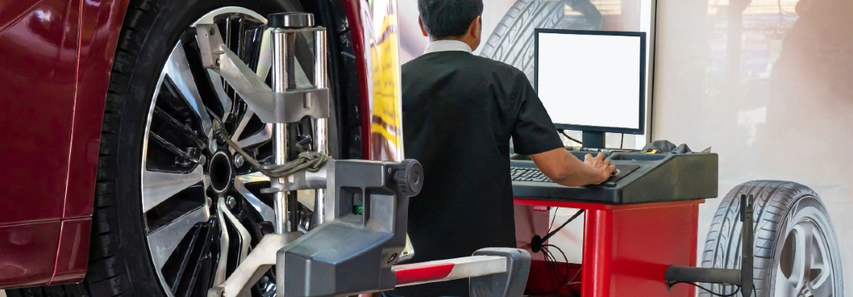 service tech doing wheel alignment