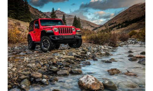 2019 Jeep Wrangler Rubicon exterior shot with red paint color driving on rocky mountain terrain near a creek