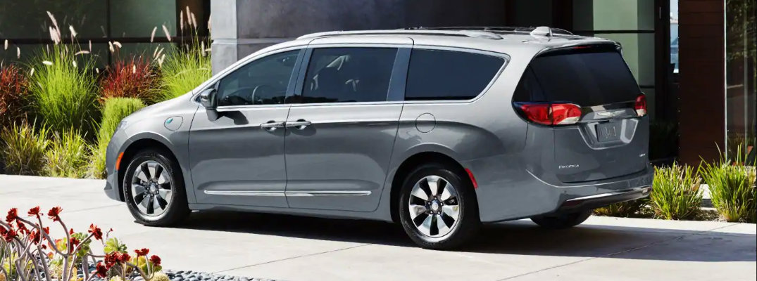2019 Chrysler Pacifica minivan exterior side rear shot with silver paint color parked outside a fancy building on a sidewalk near rocks and flora